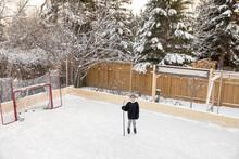 Portrait Confident Boy With Hockey Stick On Snowy Backyard Ice Rink