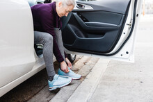 Female Runner Tying Shoelace From Car At Curb