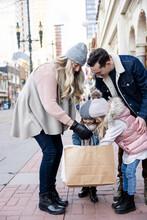 Family Looking Inside Shopping Bag On Urban Winter Sidewalk
