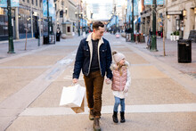 Father And Daughter With Shopping Bags Holding Hands In Winter City