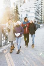 Family In Winter Coats Walking On Sunny Urban Footbridge