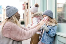 Mother Putting Face Mask On Daughter At Storefront In Winter