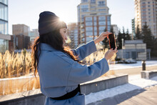 Young Woman Taking Selfie In Sunny Urban Winter Park