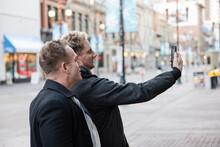 Gay Male Couple Taking Selfie On City Street