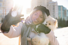 Happy Young Woman Taking Selfie With Small Dog In Sunny Winter City