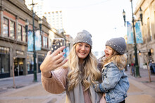 Happy Mother And Daughter In Knit Hats Taking Selfie In Winter City