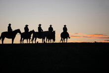 Silhouette Of Cowboys And Horses At Sunset