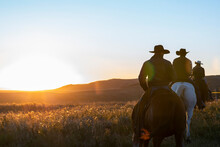Rear View Of Cowboys And Horses At Sunset