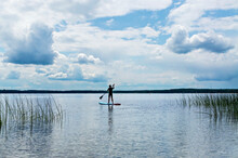 Young Man From The Back In Black Thermal Suit Paddleboarding On Blue Stand Up Paddle Board On Lake Against Background Of Cloudy Sky, Male Silhouette, Active Lifestyle, Outdoor Activities, Sup