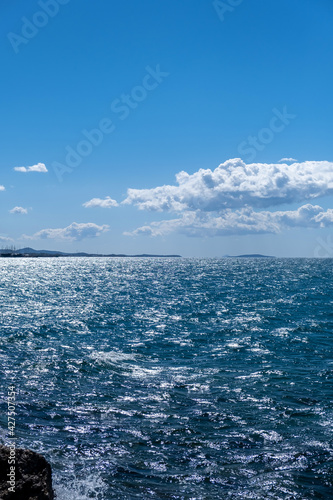 Blue sea and sky background, blue shades and white clouds.
