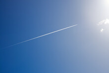 White Trail From A Military Aircraft High In The Blue Sky, Supersonic Fighter In Flight On A Sunny Day