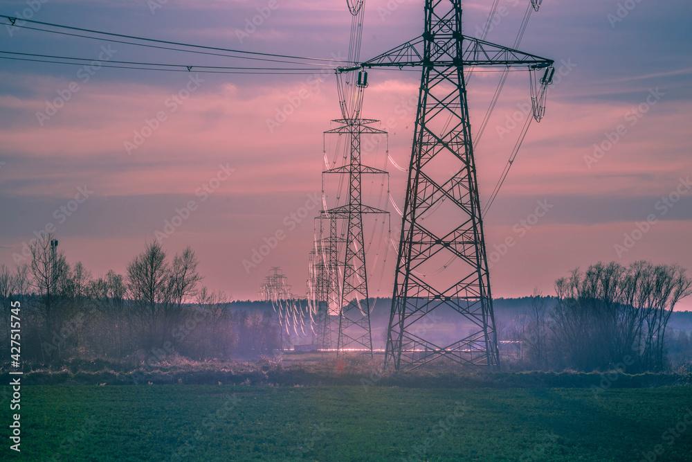 Linia elektryczna wysokiego napięcia oświetlona promieniami słonecznymi. - obrazy, fototapety, plakaty