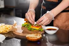 Cook Preparing Burger Adding Bacon On The Wodden Board