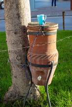 Public Big Clay Jug With Drinking Water With A Plastic Blue Cup On A Rope Stands On A Tripod Near A Tree On A Street In Tangier, Morocco