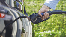 Hand Plugging In EV Car Charger Or Electric Vehicle. Cable Connect To Gas Station,power Supply Battery Charging An Alternative Sustainable Eco Environment Friendly Future Technology Energy Innovation