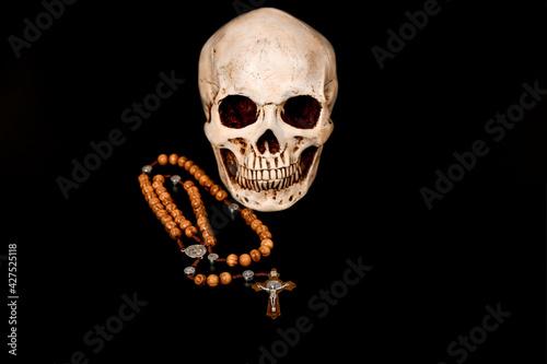 Fototapeta Human skull with catholic rosary on black background.