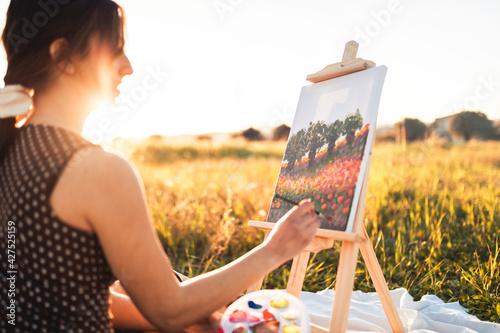 Giovane bella ragazza dipinge il quadro su tela seduta su un prato in campagna