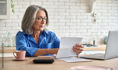 Fototapeta Adult senior 60s woman working at home at laptop. Serious middle aged woman at table holding document calculating bank loan payments, taxes, fees, retirement finances online with computer technologies obraz