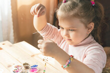 A Little Girl Is Engaged In Needlework, Making Jewelry With Her Own Hands, Stringing Multi-colored Beads On A Thread