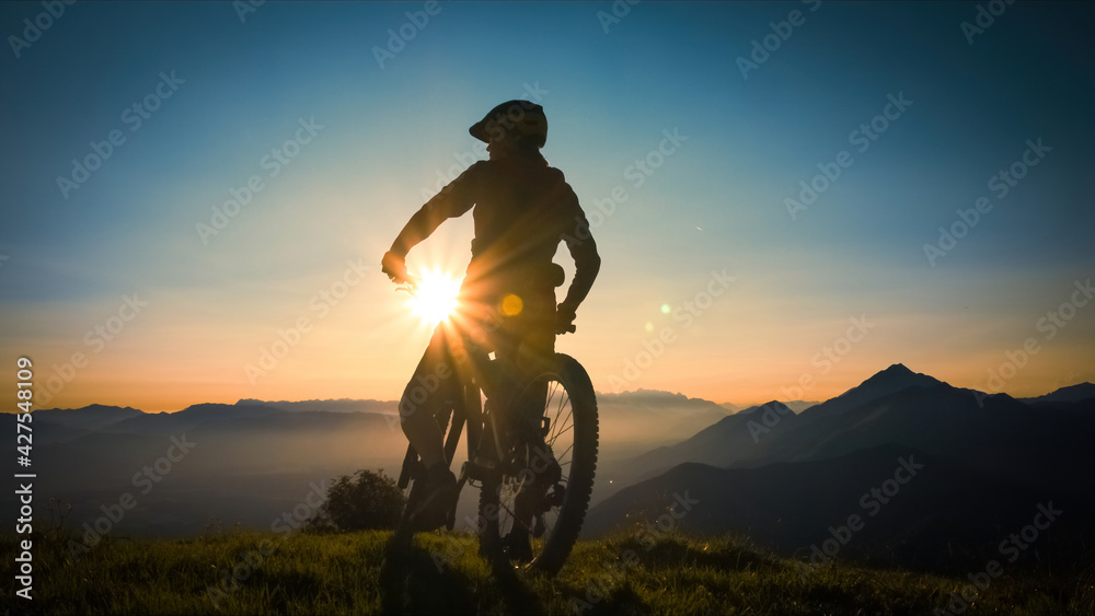 Fototapeta Silhouette of a woman on mountain bike looking at sunset