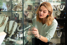 Interested Female Client Admiring Jewelry And Figurines From Natural Gemstones In Glass Showcase In Boutique