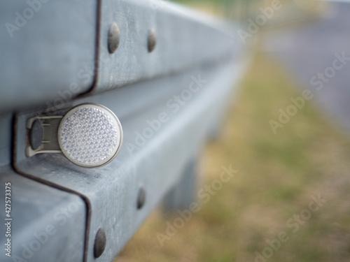 znacznik granicy drogi, odblask, na ogrodzeniu energochłonnym