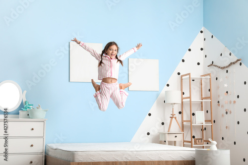 Funny little girl jumping on bed
