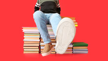 Cute Little Boy With Many Books On Color Background