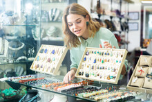 Cheerful Girl Trying On And Choosing Natural Stone Necklace In Jewerely Shop