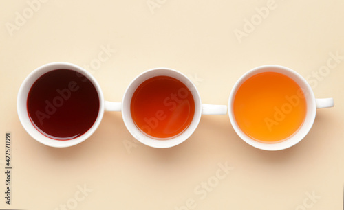Cups with different types of hot tea on color background