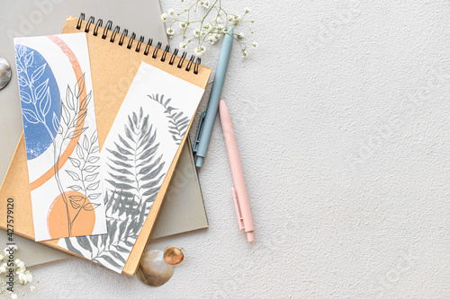 Obraz Notebooks with bookmarks and flowers on light background - fototapety do salonu
