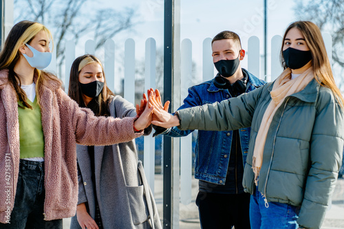 Fotografie, Obraz Variety of gay students in facial masks give high fives to greet each other