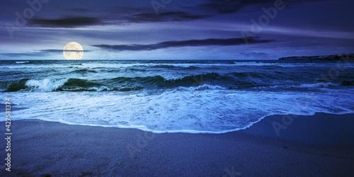 Fototapeta sea tide on a cloudy sunrise. green waves crashing golden sandy beach in full moon light. storm weather approaching. summer holiday concept obraz