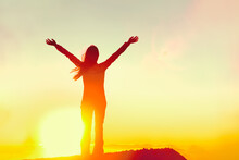 Happy Woman Sihouette With Arms Raised Up In Success Celebrating Reaching Life Goal On Sunset Glow Sunshine Sunrise. Wellness, Financial Freedom, Healthy Life Concept Background.