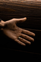Vertical Shot Of Male Hand Palm With A Ring On Wooden Background