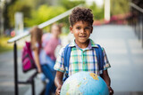 Little boy holding globe. Group of elementary age schoolchildren outside. Focus is on foreground.