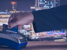 Businessman Use Card Payment Into Mobile Credit Card Reader And Hand Entering Security Pin In Credit Card Machine On World Map Background. Buy And Sell Products And Service Concept.