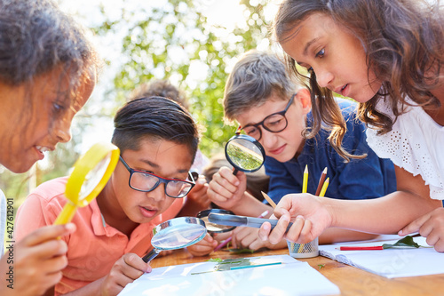 Obraz Neugierige Kinder betrachten Blatt unter Lupe - fototapety do salonu