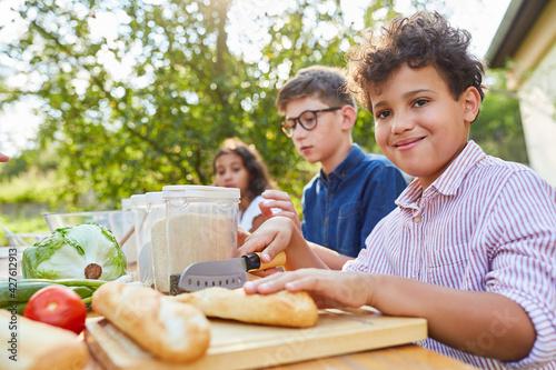 Kinder im Kochkurs im Sommercamp bereiten Salat zu