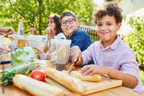 Junge im Kochkurs schneidet Baguette für einen Salat
