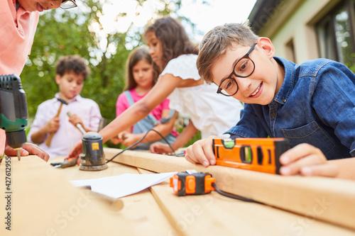 Junge mit Wasserwaage hat Spaß beim werken mit Holz - fototapety na wymiar