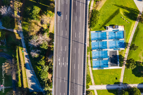 Aerial view of a car driving on the highway by some tennis courtyards in the grass in Lisbon outskirt, Portugal Wallpaper Mural