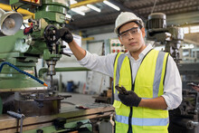 Portrait Of An Handsome Engineer In A Factory. Asian Mechanical Engineer Operating Industrial Lathe Machine.