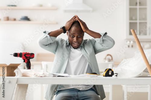 Obraz Frightened handyman having problems in assembling new furniture, sitting in kitchen interior - fototapety do salonu