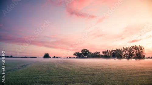 Canvas Print Meadows covered with ground fog and sunrise in the early morning.