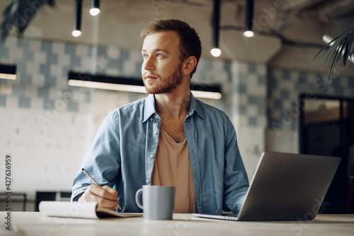 Obraz Young businessman making notes in notepad while sitting at the working table in modern office - fototapety do salonu