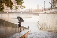 Brunette Girl In A Black Jacket Walks On The River Embankment