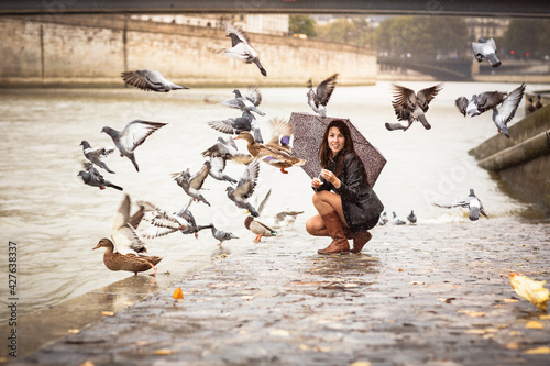 A woman with an umbrella feeds birds on the embankment of the river Fototapet