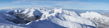 Magnificent Panoramic Shot Of Mountain Peaks Covered In Snow During The Winter Season. A Blue Sky With Few White Clouds Can Be Seen In The Background. Zakopane - Kasprowy Wierch