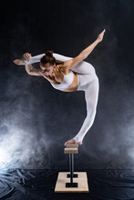 Flexible Circus Artist - Female Acrobat Doing Handstand On The Back And Smoker Background. Concept Of Willpower And Passion.